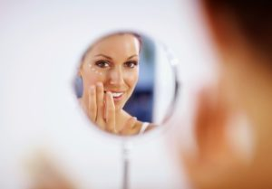 Woman looking at results of a chemical peel from The Dermatology Clinic
