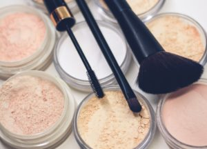 Several open containers of makeup with brushes sitting on top